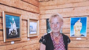 Taiteilija Stina Engvall kuvattuna Galleria Gottorpissa, taustalla hänen maalauksiaan seinällä.