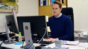 Andreas Hollsten sitter vid sitt skrivbord och jobbar.