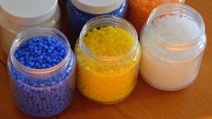 tre små plastburkar med blåa, gula och vita små pellets inuti.