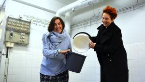 Maikku Huovila och Katja Sågbom med ämbaren i tvätteriet.