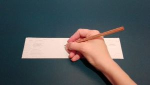 En hand håller i en penna vid en vit papperslapp.