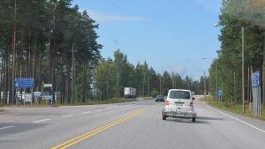 Bilar kör på en riksväg. I bakgrunden till vänster syns en rastplats.