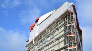 Byggställningar och tälttak på stort hus