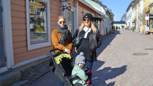Två unga kvinnor och ett barn i kärra i gamla stan i Borgå. Kvinnorna tittar in i kameran och ler. Bakom dem synns en kullerstensgata och trähus.