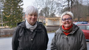 Två kvinnor utomhus med en julgran i bakgrunden.