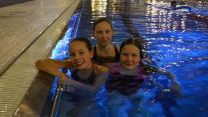 Tre flickor i en simbassäng.