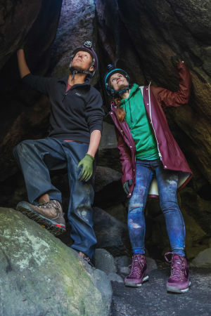 Mies ja nainen kypärissä ja otsalampuissa seisovat luolan suulla katsoen ylöspäin aukkoa, josta pilkottaa päivänvaloa.