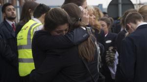 Människor tröstar varandra efter explosioner vid flygplatsen i Bryssel.