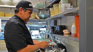 Kocken Richard Agbada sorterar köksredskap i restaurangköket.