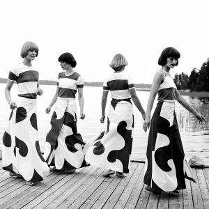 """Yleisradion televisio-ohjelma """"Ilmiömäisiä suomalaisia: Armi Ratia"""". Naisia, neljä naismallia esittelemässä Marimekon vaatteita. Muotinäytös."""