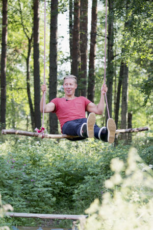 Toimittaja Nicke Aldén puuhun ripustetussa keinussa Varjakansaaressa Oulussa, taustalla kesäinen metsä.
