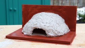 En fågelholk för hussvalor byggd av betong och rödmåladfanér.