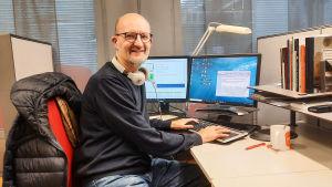 En man sitter bakom ett skrivbord. Han tittar in i kameran och ler.