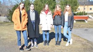 Fem unga kvinnor står framför kameran. Klädda i vinterrrockar på en skolgård. Ekenäs gymnasium.