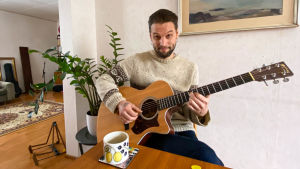 En man som sitter och spelar gitarr vid matbordet.