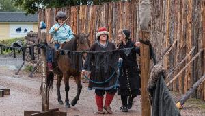 Lapsi istuu hevosen selässä puinen keppi kädessään, vieressä aikuinen taluttamassa hevosta.