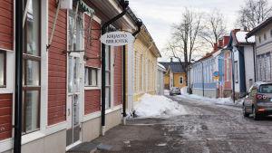 Vy av Drottninggatan mot Neristan. Till vänster i bild synns biblioteksbyggnaden och en skylt där det står kirjasto bibliotek.