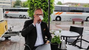 En man i kavaj sitter utomhus vid ett café och dricker kaffe ur en pappmugg.