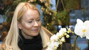 Susanne tittar på vita orkidéer i en blomaffär.