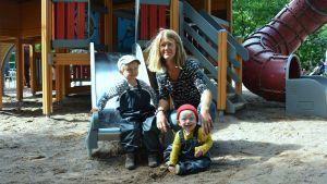 Sara Wilson med sina söner Åke och Allan framför en rutschkana.