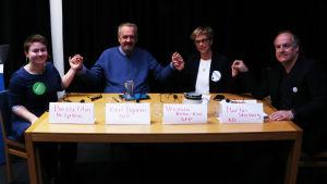 Fyra personer sitter vid ett bord och håller varandra i händerna.