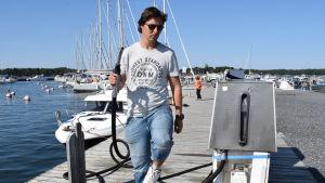 Andreas Öhman med en tankingspistol i handen på bryggan i Kasnäs gästhamn i soligt sommarväder.