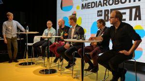 kuusi miestä istuu pöytien ääressä, takaseinällä Yle Beta Day, mediarobotit -juliste