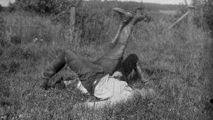 """Två män leker """"bryta stubbar"""". Bilden är tagen 1930 i Bromarf."""