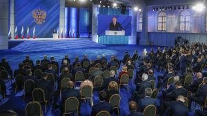En stor hall, Vladimir Putin står på scen och håller tal.