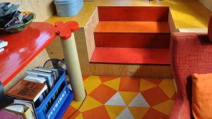 Ett rum i översta våningen med orange, gult och rött.