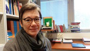 Niina Junttila, en dam med glasögon och grånande hår och grå tröja, sitter i sitt arbetsrum med böcker, skrivbord och en spjälgardin.