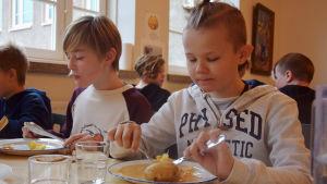 Två pojkar sitter och äter skolmat i en matsal.