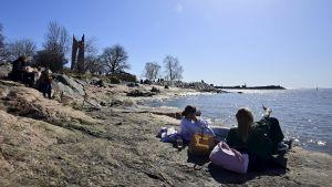 Människor njuter av det soliga vårvädret vid Eira strand i Helsingfors den 18 april 2021.