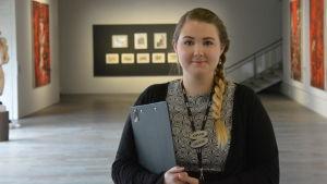 En flicka med fläta som jobbar som guide på en konstutställning