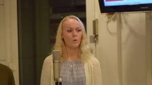 Anna Malmsten sjunger framför en mikrofon.