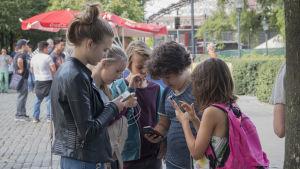Barn står i en park och spelar Pokémon Go.