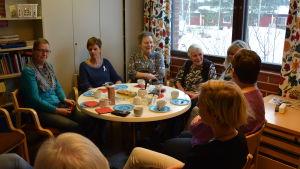 Sju damer sitter kring ett runt bord. En av dem har ett rosa band, för bröstcancer, på sin tröja.