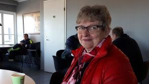 Kvinna sitter vid bord med kaffekopp.
