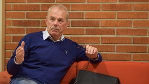 Ulf Heimberg sitter på en soffa.