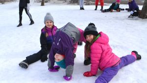 Två flickor gör spagat och en gör brygga, på snöig skolgård.