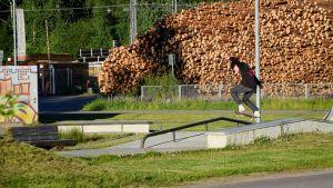 En bild på en pojke i svart tröja och mössa som hoppar med en skejtboard på en skejtramp. I bakgrunden syns stockhögar.