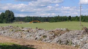 Stora jordvallar på en åker. Långt borta syns en gul grävmaskin.