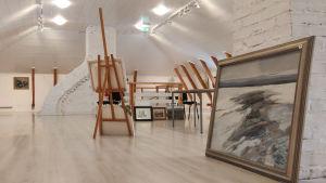 Vy över ett stort ljust rum med tavlor på stafflin och väggar.