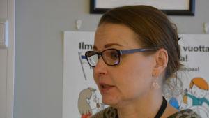 Kati Järvi, en dam med glasögon och ett örhänge med två hjärtan, är chef för inomhusluft i Åbo stad.
