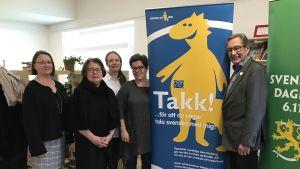 Alla fem från arrangörsgruppen uppställda vid två planscher, på den ena syns Svenni på den andra står det Svenska dagen.