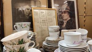 Olika kaffekoppar på ett bord framför inramade fotografier på två kvinnor samt ett inramat betyg.