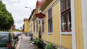 Ett gult trähus invid en gata. På en skylt står det Almska gården.