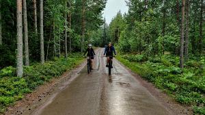 En man och en kvinna cyklar på en sandväg.