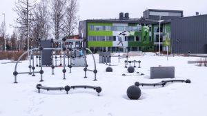 Olika ställningar och gymredskap i snön utanför en grön byggnad.
