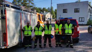 Fem män i gula västar står vid en brandbil. Bakom dem en vit byggnad och en gul träbyggnad.